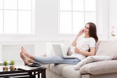 Νέα γυναίκα που μιλά σε κινητό στο σπίτι στον καναπέ Σκοτεινός-μαλλιαρό κορίτσι σε περιστασιακό Στοκ φωτογραφία με δικαίωμα ελεύθερης χρήσης