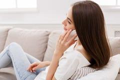 Νέα γυναίκα που μιλά σε κινητό στο σπίτι στον καναπέ Στοκ Εικόνες