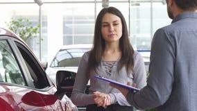 Νέα γυναίκα που μιλά στον πωλητή στη εμπορία αυτοκινήτων απόθεμα βίντεο