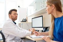 Νέα γυναίκα που μιλά στο γιατρό στοκ εικόνα