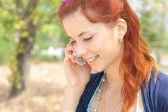 Νέα γυναίκα που μιλά στο τηλέφωνο και που χαμογελά υπαίθρια Στοκ Εικόνα
