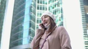 Νέα γυναίκα που μιλά στο τηλέφωνο μεταξύ των ψηλών κτιρίων μιας μεγαλούπολης φιλμ μικρού μήκους