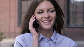 Νέα γυναίκα που μιλά στο τηλέφωνο στεμένος υπαίθριος απόθεμα βίντεο