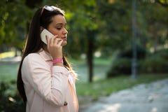 Νέα γυναίκα που μιλά στο smartphone σοβαρά υπαίθρια στο πάρκο Στοκ εικόνα με δικαίωμα ελεύθερης χρήσης