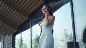 Νέα γυναίκα που μιλά τηλεφωνικώς στο υπόβαθρο των λαμπρών πορτών απόθεμα βίντεο