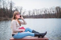 Νέα γυναίκα που μιλά με το τηλέφωνο, με το βιβλίο σε ετοιμότητα της, τον καθημερινό τρόπο ζωής, ποταμός στο υπόβαθρο, άνοιξη, ηλι στοκ εικόνα με δικαίωμα ελεύθερης χρήσης