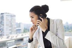 Νέα γυναίκα που μιλά πέρα από το τηλέφωνο Στοκ Φωτογραφίες