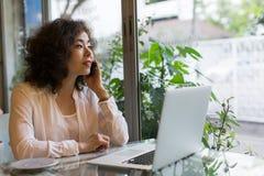Νέα γυναίκα που μιλά σε κινητό καθμένος σε έναν καφέ με ένα lap-top Στοκ Εικόνες
