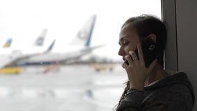 Νέα γυναίκα που μιλά στο έξυπνο τηλέφωνο στον αερολιμένα με το αεροπλάνο στο υπόβαθρο απόθεμα βίντεο