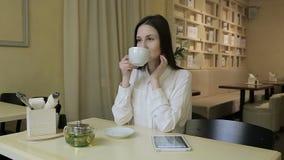 Νέα γυναίκα που μιλά στο κινητό τηλέφωνο στον καφέ απόθεμα βίντεο