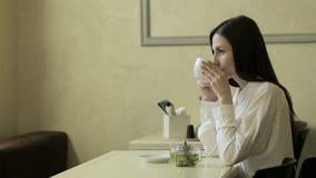 Νέα γυναίκα που μιλά στο κινητό τηλέφωνο στον καφέ φιλμ μικρού μήκους