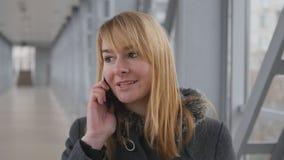 Νέα γυναίκα που μιλά στο τηλέφωνο και τον περίπατο στην ημέρα εσωτερική Πορτρέτο της ελκυστικής ομιλίας κοριτσιών στο κινητό τηλέ απόθεμα βίντεο