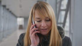 Νέα γυναίκα που μιλά στο τηλέφωνο και τον περίπατο στην ημέρα εσωτερική Πορτρέτο της ελκυστικής ομιλίας κοριτσιών στο κινητό τηλέ φιλμ μικρού μήκους