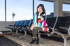 Νέα γυναίκα που μιλά στο τηλέφωνο στον αερολιμένα Στοκ Φωτογραφίες