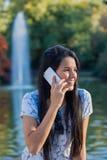 Νέα γυναίκα που μιλά στο τηλέφωνο στο πάρκο στοκ φωτογραφία