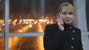 Νέα γυναίκα που μιλά στο τηλέφωνο το βράδυ εσωτερικό Πορτρέτο της ελκυστικής ομιλίας κοριτσιών στο κινητό τηλέφωνο κλείστε επάνω φιλμ μικρού μήκους