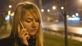 Νέα γυναίκα που μιλά στο τηλέφωνο το βράδυ υπαίθριο Πορτρέτο της ελκυστικής ομιλίας κοριτσιών στο κινητό τηλέφωνο κλείστε επάνω απόθεμα βίντεο