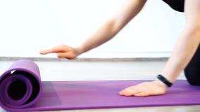 Νέα γυναίκα που ξετυλίγει ένα χαλί για την άσκηση της γιόγκας στο στούντιο απόθεμα βίντεο
