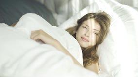 Νέα γυναίκα που ξυπνά και που χαμογελά απόθεμα βίντεο