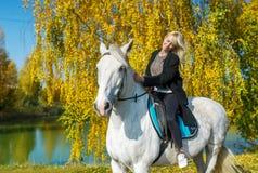 Νέα γυναίκα που οδηγά ένα άλογο σε μια ηλιόλουστη ημέρα φθινοπώρου στα πλαίσια της μπλε λίμνης Στοκ Φωτογραφία
