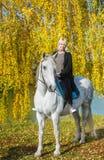 Νέα γυναίκα που οδηγά ένα άλογο σε μια ηλιόλουστη ημέρα φθινοπώρου στα πλαίσια του χρυσού φθινοπώρου Στοκ Εικόνες