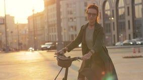 Νέα γυναίκα που οδηγά στο ποδήλατο να εξισώσει την πόλη και να εξετάσει τη κάμερα απόθεμα βίντεο