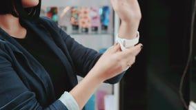 Νέα γυναίκα που δοκιμάζει το νέο έξυπνο ρολόι Έξυπνο ρολόι Η νέα γυναίκα επιλέγει να αγοράσει τα έξυπνα ρολόγια στο κατάστημα Αγο απόθεμα βίντεο