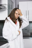Νέα γυναίκα που πάσχει από τον πονοκέφαλο που στέκεται στην κουζίνα Στοκ φωτογραφία με δικαίωμα ελεύθερης χρήσης