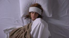 Νέα γυναίκα που πάσχει από τον υψηλό πυρετό, που βρίσκεται στο κρεβάτι με τη συμπίεση στο μέτωπο φιλμ μικρού μήκους