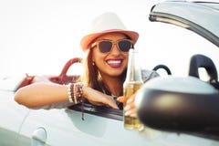 Νέα γυναίκα που πίνει μια μπύρα και που φαίνεται το ηλιοβασίλεμα Κάθεται σε ένα αθλητικό αυτοκίνητο Στοκ Φωτογραφία