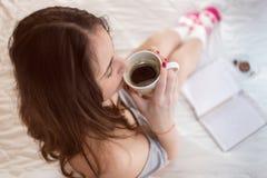 Νέα γυναίκα που πίνει τον καφέ της στο κρεβάτι Στοκ Εικόνες