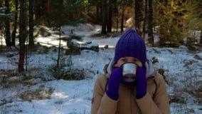 Νέα γυναίκα που πίνει το καυτό τσάι ή τον καφέ στο χειμερινό δάσος απόθεμα βίντεο