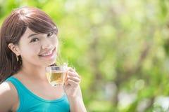 Νέα γυναίκα που πίνει το καυτό τσάι στοκ φωτογραφία