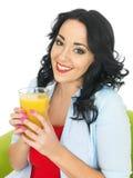 Νέα γυναίκα που πίνει το φρέσκο χυμό από πορτοκάλι Στοκ φωτογραφία με δικαίωμα ελεύθερης χρήσης