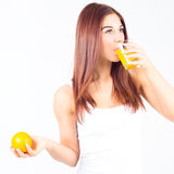 Νέα γυναίκα που πίνει το χυμό από πορτοκάλι και που κρατά το πορτοκάλι στο χέρι της Υγιής τρόπος ζωής Στοκ εικόνα με δικαίωμα ελεύθερης χρήσης
