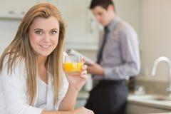 Νέα γυναίκα που πίνει το χυμό από πορτοκάλι στην κουζίνα Στοκ φωτογραφία με δικαίωμα ελεύθερης χρήσης