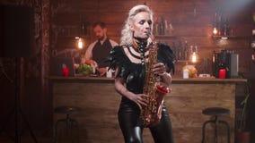 Νέα γυναίκα που παίζει παθιασμένα ένα ρομαντικό τραγούδι σε ένα saxophone μπροστά από έναν μετρητή φραγμών απόθεμα βίντεο