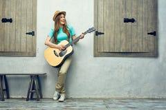 Νέα γυναίκα που παίζει την ακουστική κιθάρα Στοκ φωτογραφία με δικαίωμα ελεύθερης χρήσης