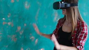 Νέα γυναίκα που παίζει το τηλεοπτικό παιχνίδι με την κάσκα εικονικής πραγματικότητας χαρτονιού απόθεμα βίντεο