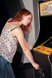 Νέα γυναίκα που παίζει arcade Στοκ Φωτογραφίες