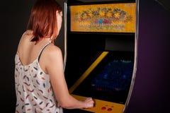 Νέα γυναίκα που παίζει arcade Στοκ Εικόνα