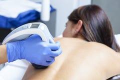 Νέα γυναίκα που παίρνει ένα anticellulite και μια περιοριστική θεραπεία σωμάτων σε μια SPA υγείας Στοκ Εικόνες
