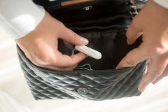 Νέα γυναίκα που παίρνει εμμηνορροϊκό tampon από το πορτοφόλι Στοκ φωτογραφίες με δικαίωμα ελεύθερης χρήσης