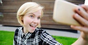 Νέα γυναίκα που παίρνει μια αυτοπροσωπογραφία με το έξυπνο τηλέφωνο στοκ φωτογραφία