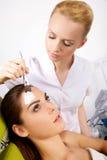Νέα γυναίκα που παίρνει την επεξεργασία μασκών δερμάτων ομορφιάς στο πρόσωπό της με Στοκ Εικόνες