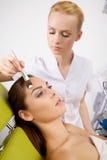 Νέα γυναίκα που παίρνει την επεξεργασία μασκών δερμάτων ομορφιάς στο πρόσωπό της με Στοκ Φωτογραφία