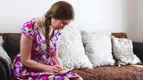 Νέα γυναίκα που παίρνει τις σημειώσεις για τον καναπέ της απόθεμα βίντεο