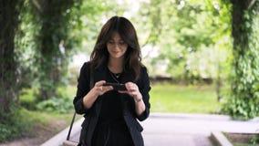 Νέα γυναίκα που παίρνει τις τηλεφωνικές εικόνες σε ένα πάρκο φιλμ μικρού μήκους