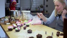 Νέα γυναίκα που παίρνει τις φωτογραφίες των cupcakes έχει ψήνει στην κουζίνα Θηλυκό smartphone χρησιμοποίησης για να πάρει τις ει απόθεμα βίντεο