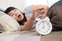 Νέα γυναίκα που παίρνει τονισμένη για να ξυπνήσει πάρα πολύ νωρίς, ρηχό Στοκ Εικόνες